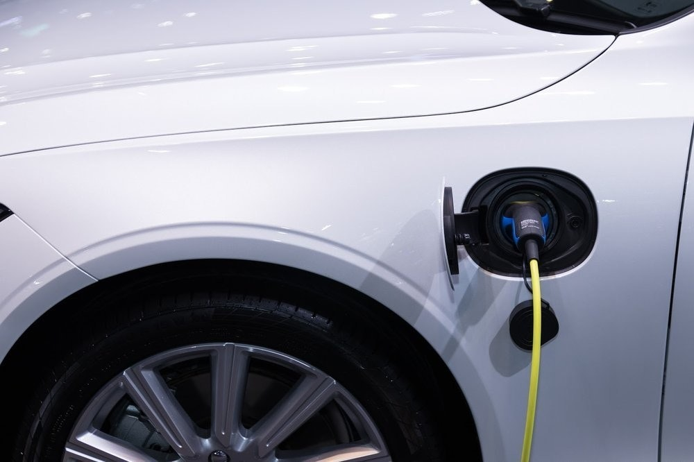 照片中包含了充電汽車混合動力車、電動車、特斯拉公司、汽車、充電站