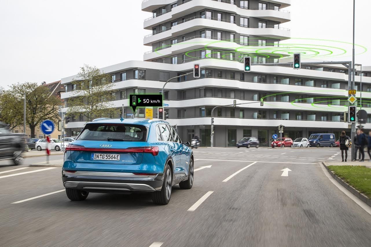 Audi, Car, Traffic light, , Traffic, Road, Green wave, Audi e-tron, Vehicle, , Traffic light, Land vehicle, Vehicle, Car, Transport, Mode of transport, Sport utility vehicle, Road, Automotive exterior, Automotive design, Family car