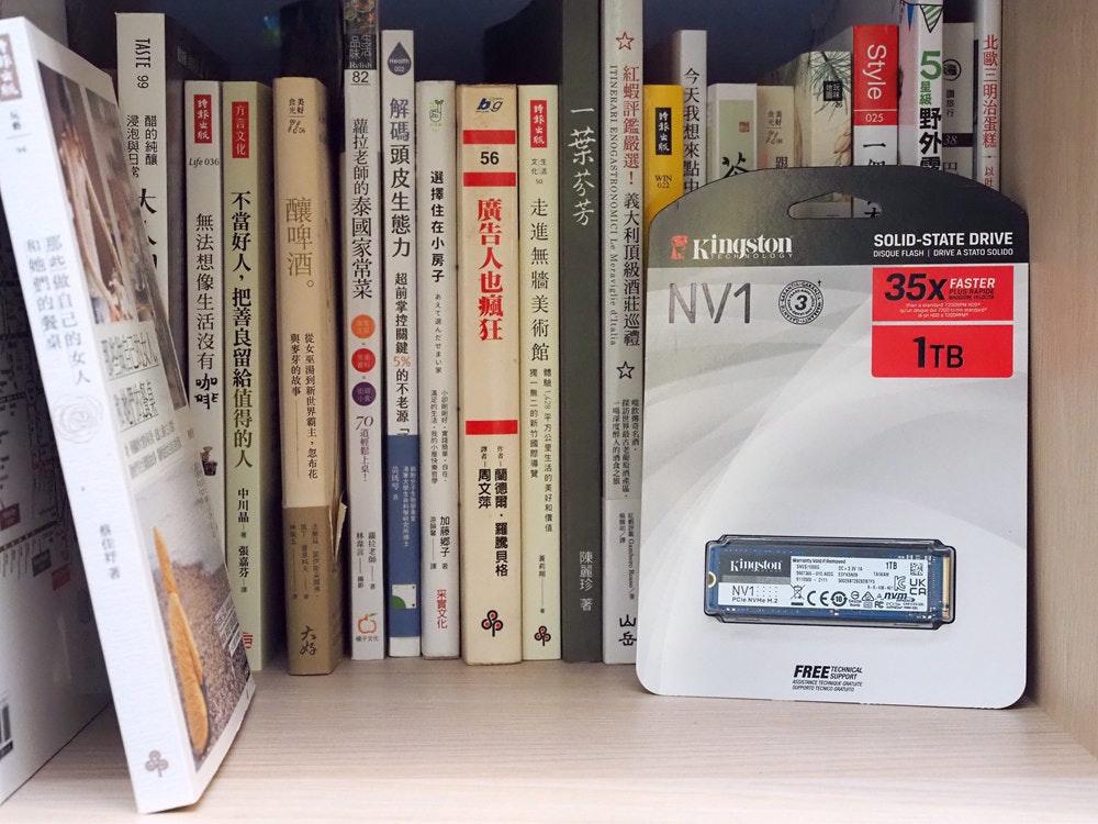 照片中提到了Kingston、SOLID-STATE DRIVE、DISQUE FLASH I DRIVE A,跟TV3拉脫維亞有關,包含了書、書櫃、架、家具類、產品設計