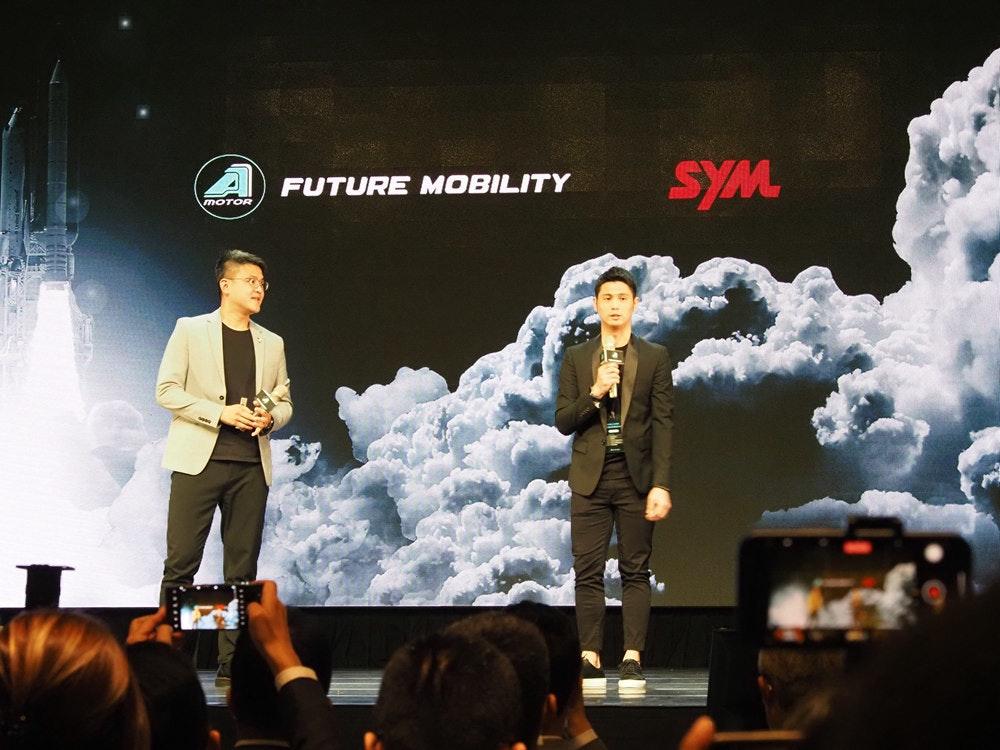 照片中提到了SYM、FUTURE MOBILITY、MOTOR,跟SYM汽車、阿達克斯石油有關,包含了階段、羅尼·多斯(Ronnie Doss)、音樂會、領導、劇院