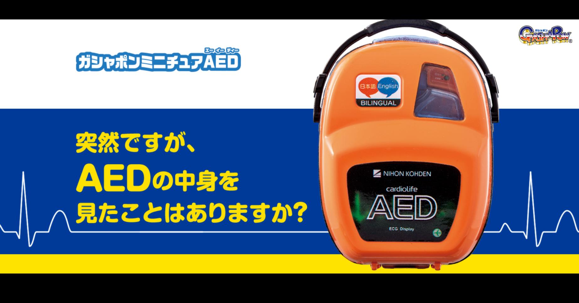 照片中提到了DポンミニチュAED、日本語Englis)、BILINGUAL,包含了松本龍、產品設計、牌、產品、儀表
